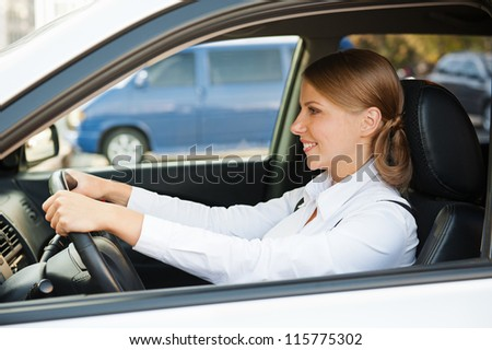 smiley and prosperous businesswoman driving the car - stock photo