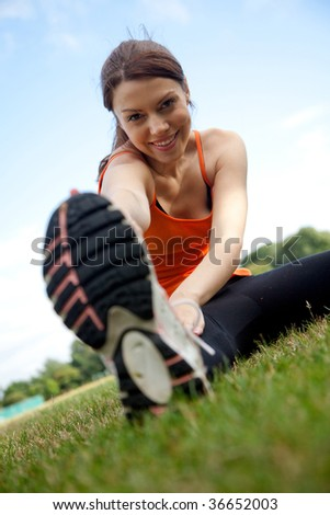 Smiley athletic woman stretching her legs outdoors - stock photo