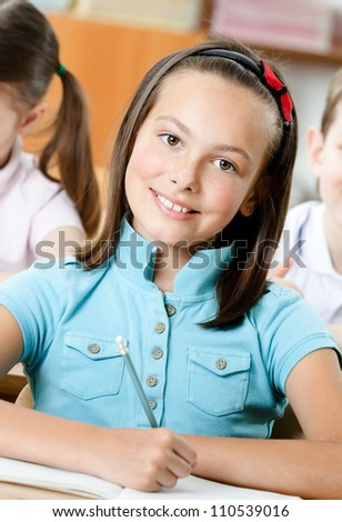 Smiley beautiful schoolgirl sits at the desk - stock photo