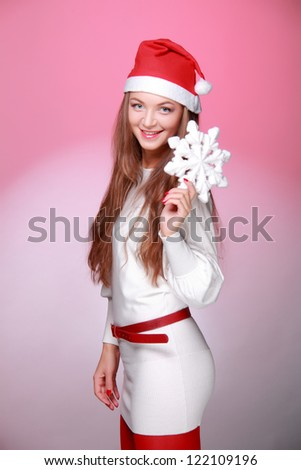 Smiley beautiful young woman posing on camera with white snowflake on Holiday theme