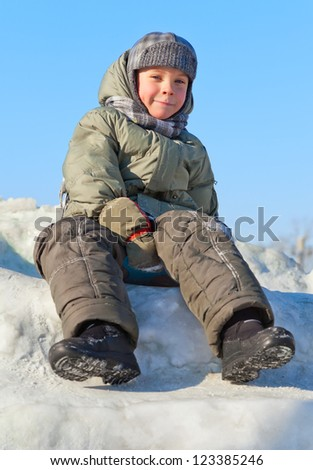 smiley boy sitting at snow with warm coat - stock photo