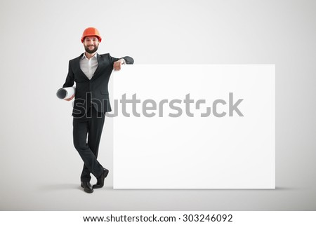 smiley businessman in formal wear and orange helmet holding big empty white banner over grey background - stock photo