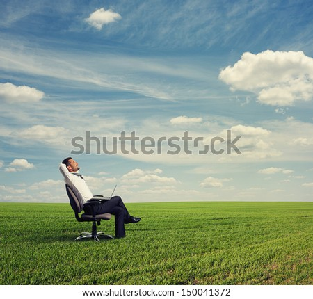 smiley businessman resting on the green field - stock photo