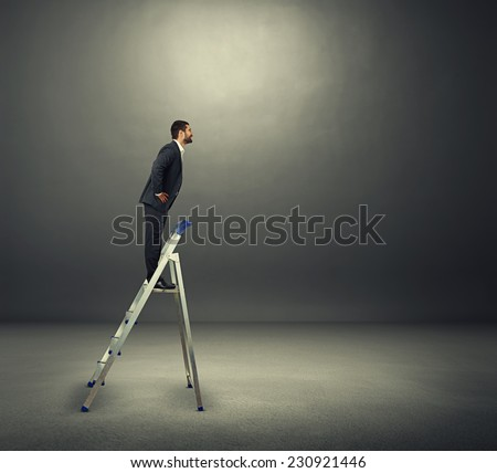 smiley businessman standing on the stepladder and looking at empty copyspace. photo in the dark room - stock photo