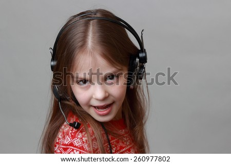 Smiley caucasian little girl wearing red christmas sweater is singing - stock photo