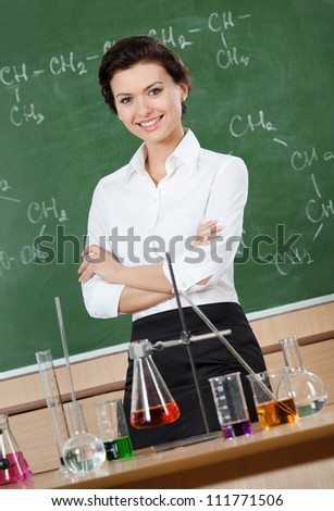 Smiley chemistry teacher with crossed arms at the classroom - stock photo