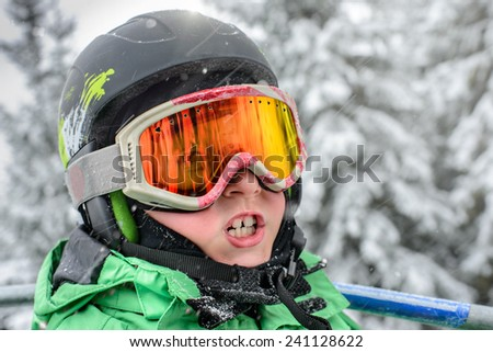 smiley child in a mountain-skiing helmet and points is represented on the ski lift - stock photo