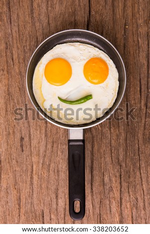 Smiley egg with chilly on a pan - stock photo