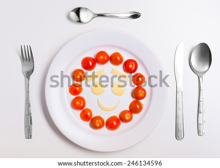 smiley face emoticon food, made from cheese and tomatoes, on a plate with cutlery, isolated