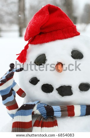 Smiley face snowman with a red hat - stock photo