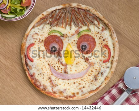 Smiley Faced Pizza with a Side Salad - stock photo