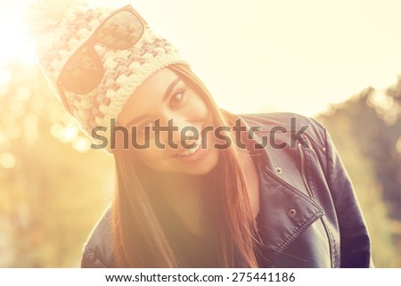 Smiley girl in a park with sun flare.