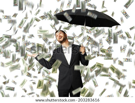 smiley glad businessman with umbrella standing under money rain and looking up - stock photo