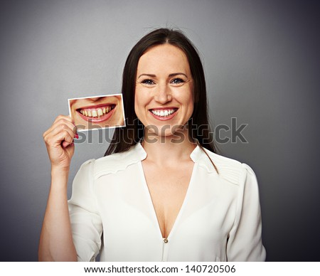 smiley healthy woman holding picture with dirty yellow teeth - stock photo