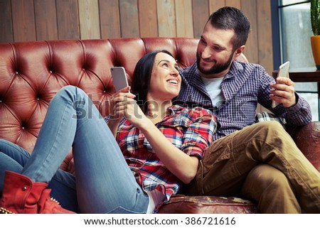 smiley man and woman resting on sofa and using smartphones
