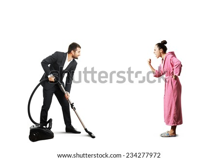 smiley man in suit holding vacuum cleaner and looking at screaming angry wife in pink dressing gown. isolated on white - stock photo