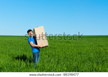 smiley messenger in blue t-shirt carrying boxes - stock photo