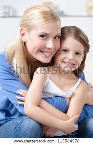 Smiley mother embraces her daughter - stock photo