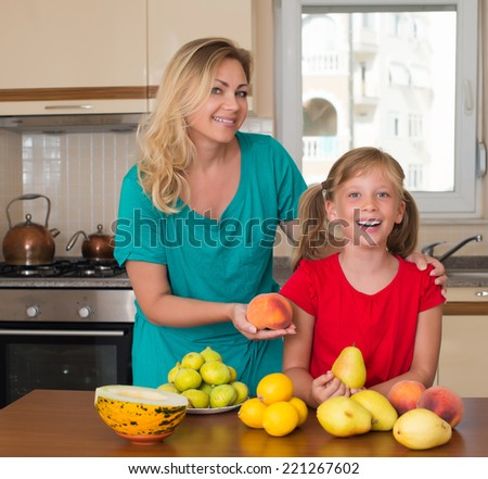Smiley mother with her keeping sweet pear daughter. Healthy eating - woman and child in the kitchen with different kinds of fruits for breakfast food - stock photo