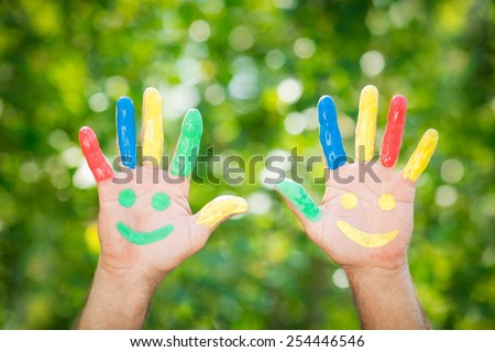 Smiley on hands against green spring background - stock photo