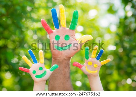 Smiley on hands against green spring blurred background. Family having fun outdoors - stock photo