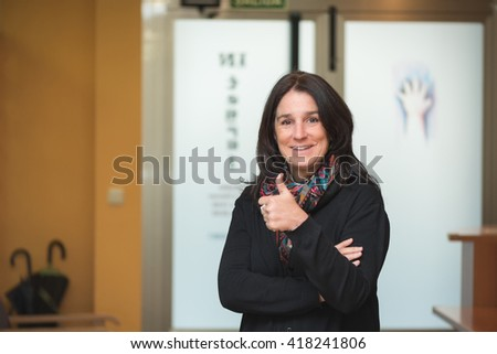 smiley professional entrepreneur middle aged brunette woman at entrance hall workplace standing, crossing arms and giving thumbs up - stock photo