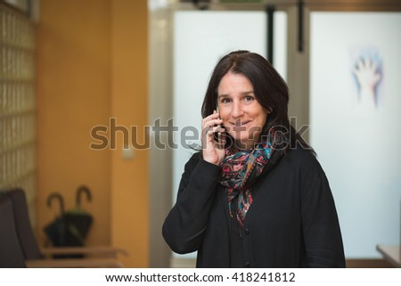 smiley professional entrepreneur middle aged brunette woman at entrance hall workplace standing and talking on phone - stock photo
