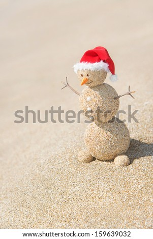 Smiley sandy snowman in red santa hat. Holiday concept for New Years and Christmas Cards. - stock photo
