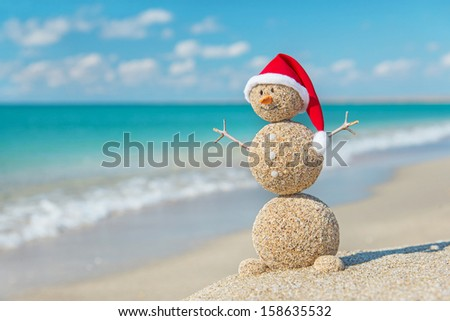 Smiley sandy snowman in santa hat. Holiday concept for New Years and Christmas Cards. - stock photo