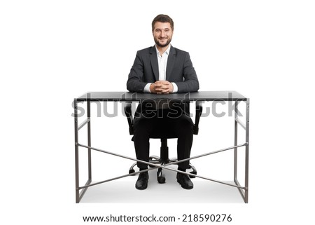 smiley successful businessman sitting at the table and looking at camera. isolated on white background - stock photo