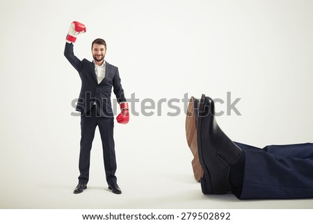 smiley winner businessman in red boxing gloves standing near big lying mans legs over light grey background - stock photo