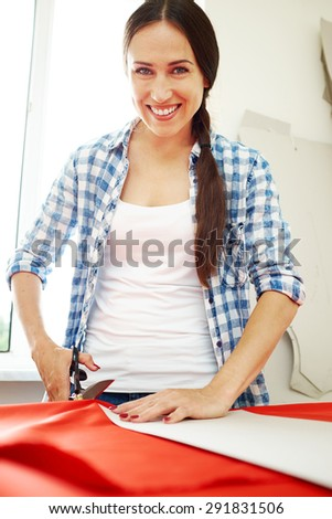 smiley woman cutting red fabric with tailors scissors and looking at camera