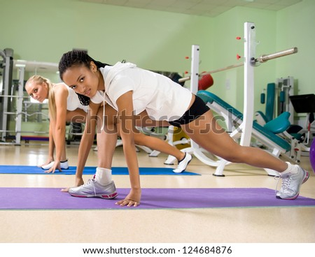 smiley woman doing exercises at the fitness club - stock photo