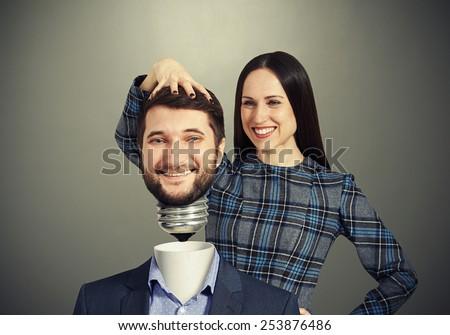 smiley woman fixing man over dark background - stock photo