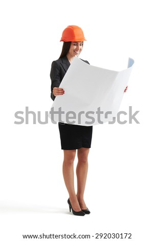 smiley woman in hardhat looking at blueprint. isolated on white background - stock photo