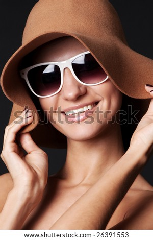 smiley woman in hat and sunglasses against black background - stock photo