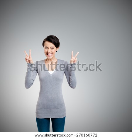 Smiley woman shows victory sign with two hands, isolated on white - stock photo