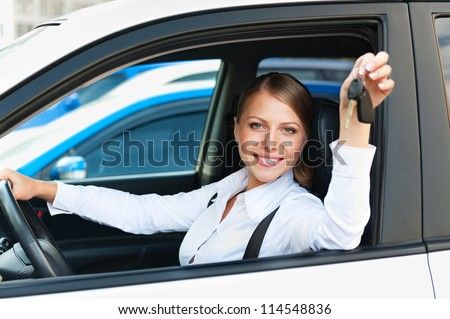smiley woman sitting in car and showing the car keys - stock photo