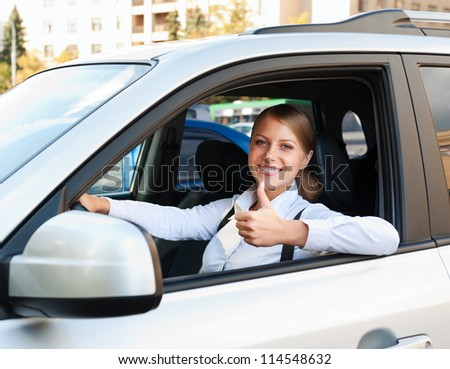smiley woman sitting in car and showing thumbs up - stock photo