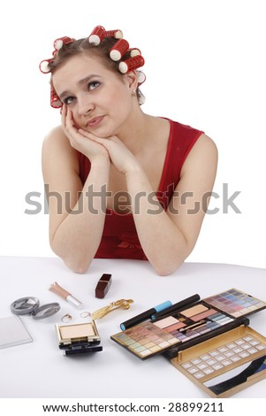 Smiley woman with hair-rollers on a white background. Nice girl with red hair-curlers. Young attractive housewife with curlers in hair is thinking about something.  Studio, white background. - stock photo