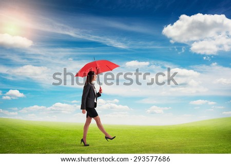 smiley woman with red umbrella walking on green field over blue sky