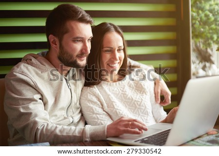smiley young adult couple using laptop in restaurant - stock photo