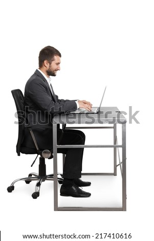 smiley young businessman sitting at the table and working with laptop. isolated on white background  - stock photo