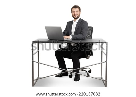 smiley young businessman sitting at the table with laptop and looking at camera. isolated on white background - stock photo
