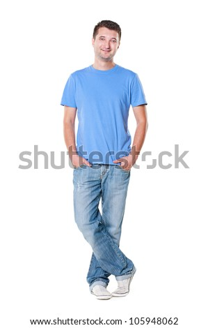 smiley young man in blue t-shirt and jeans standing with hands in pocket - stock photo
