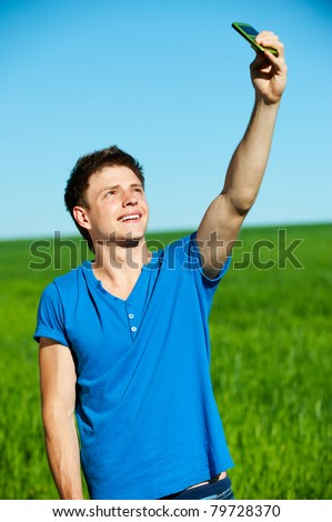smiley young man taking picture on phone against green grass and blue sky - stock photo