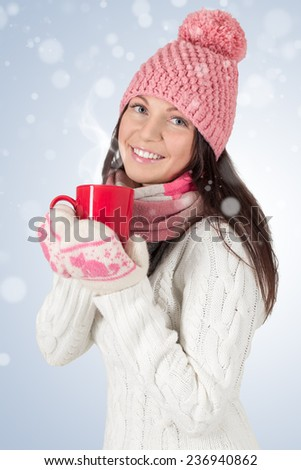 Smiley young woman in winter outfit with red cup. With snowflakes background.