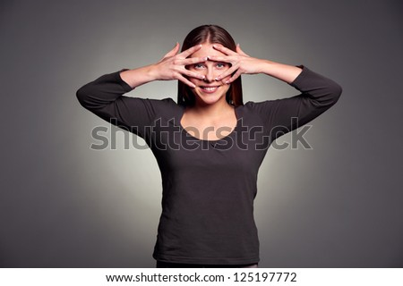 smiley young woman looking through her fingers. studio shot over dark background - stock photo