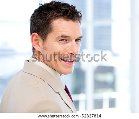 Smiliing businessman with headset on standing in a modern building - stock photo