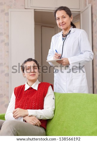 Smiliinng doctor and female patient at medical hospital - stock photo